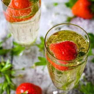 may wine in flute glasses with strawberries