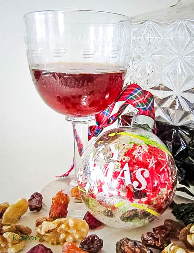 christmas cheer spiced liqueur with christmas bauble in front of glass