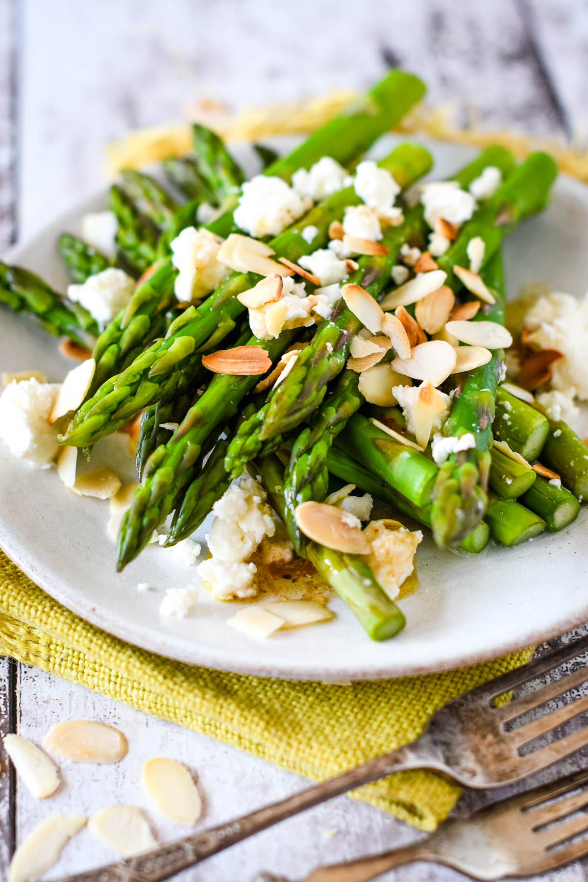 asparagus feta and almonds on white plate with fork at side
