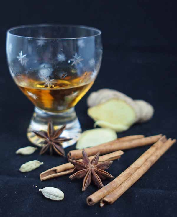 spiced rum in glass with spices beside