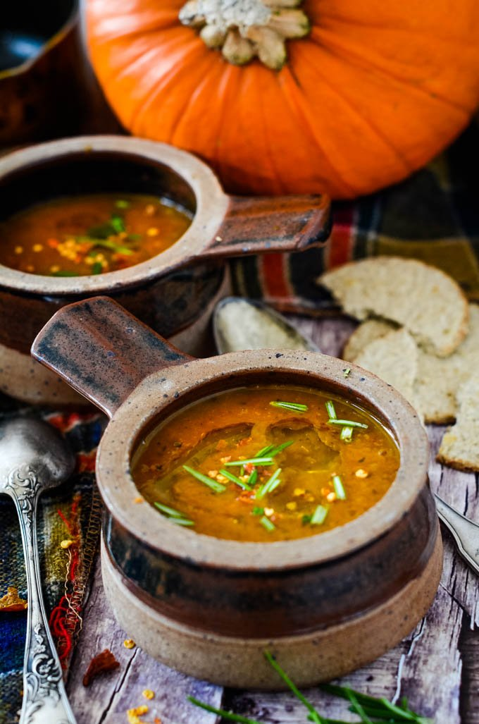 two bowls of soup with pumpkin behind