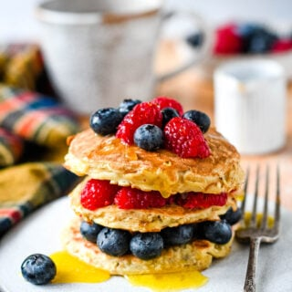 3 ingredient porridge oat pancakes on table with cup and jug in background