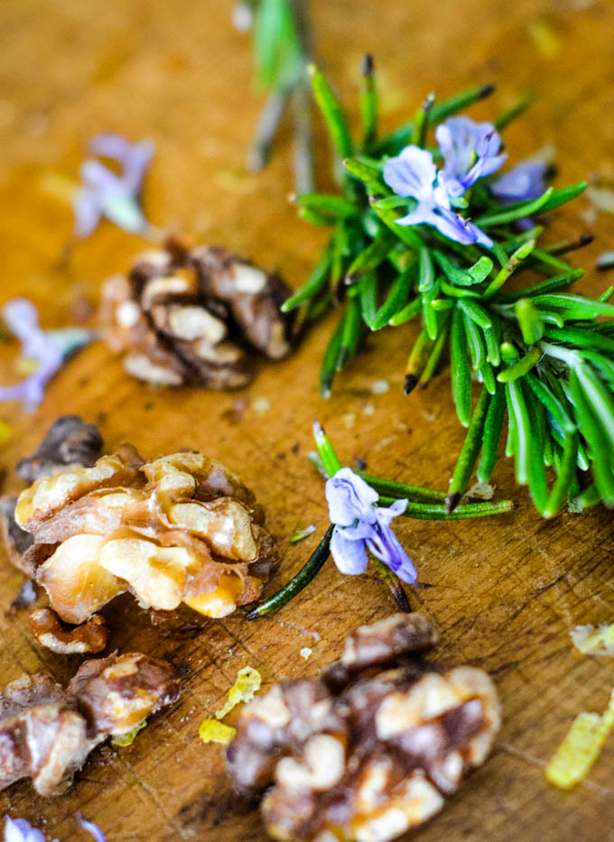 rosemary and walnuts on chopping board