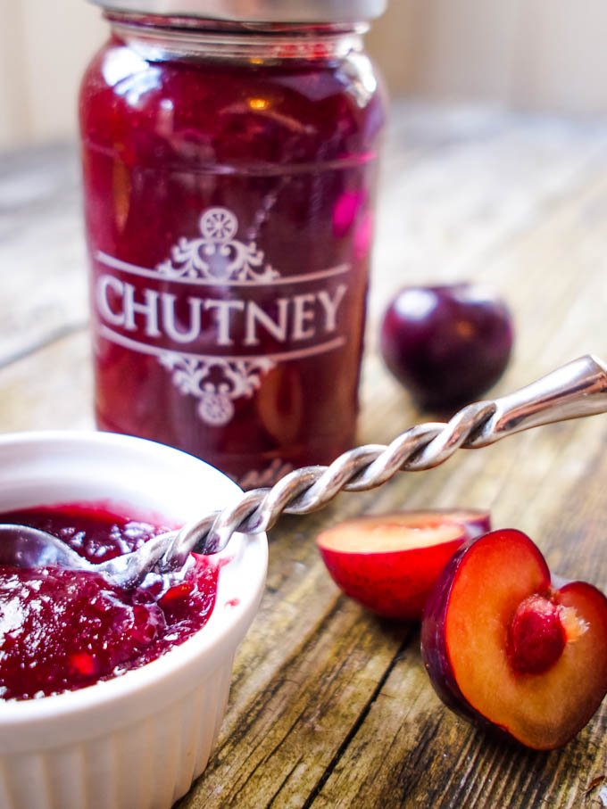 plum and ginger chutney in jar with plums at side
