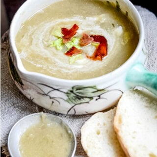 celery and apple soup with bread and spoon in front