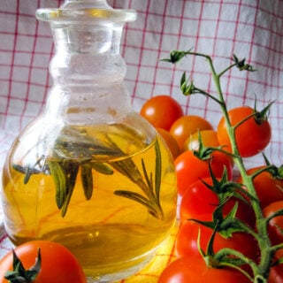 rosemary and mint vinegar in bottle with tomatoes at side