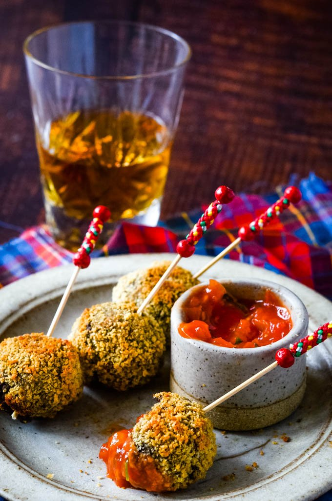 bowl of spicy dip with haggis truffles on sticks
