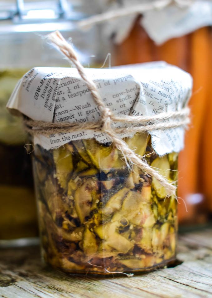 grilled courgettes in oil in jar with paper on lid