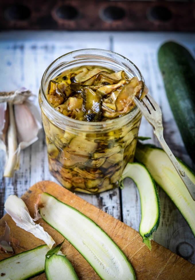 pickling fork in jar with grilled courgettes in oil