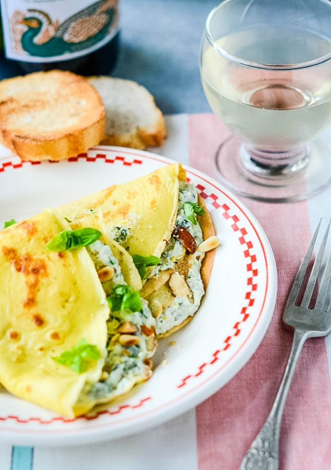 pesto filled pancakes on plate with bread and wine behind