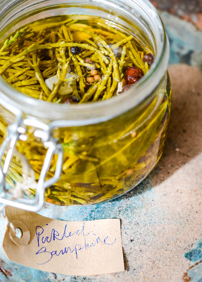 pickled samphire in large jar on a plate with sand