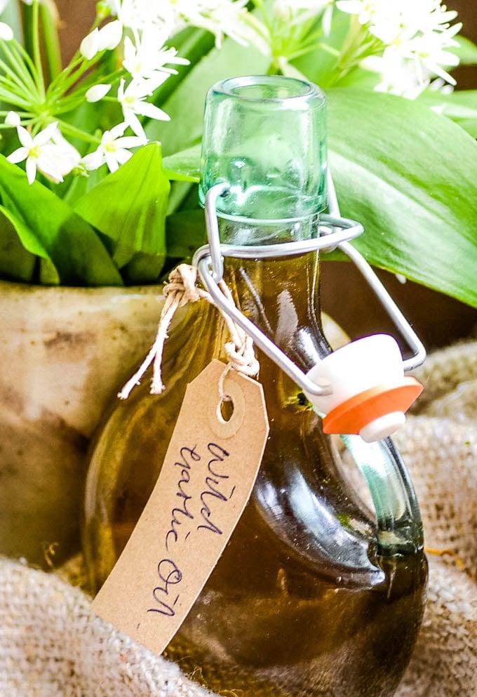wild garlic oil in old fashioned bottle with wild garlilc flowers behind