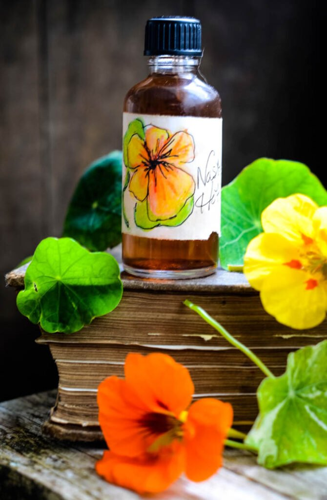 nasturtium hot sauce in bottle on top of books with nasturtium flowers