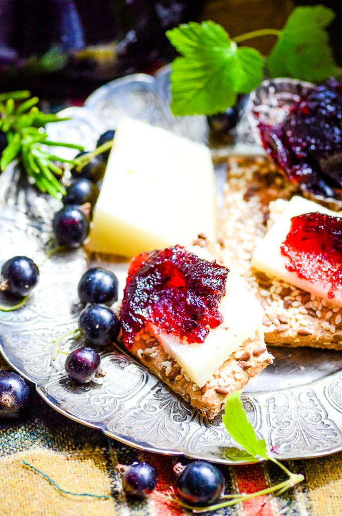 fruit cheese on crackers with blackcurrants scattered on plate