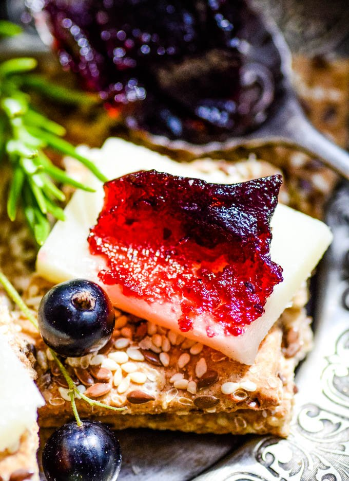 Blackcurrant and rosemary fruit cheese on a cracker with cheese