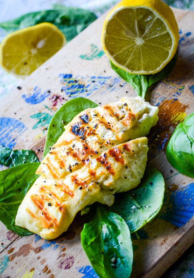 homemade halloumi cheese on spinach leaves with lemon