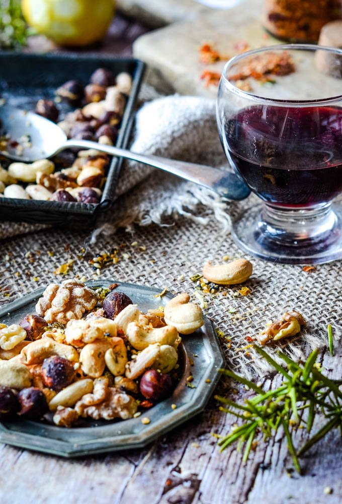 small bowl of spiced nuts with glass of red wine behind