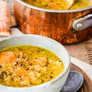 bowl of lentil soup with copper pan behind