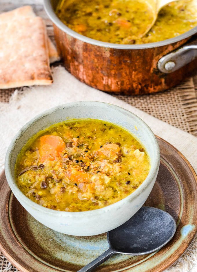 French puy lentil soup in bowl with pan behind