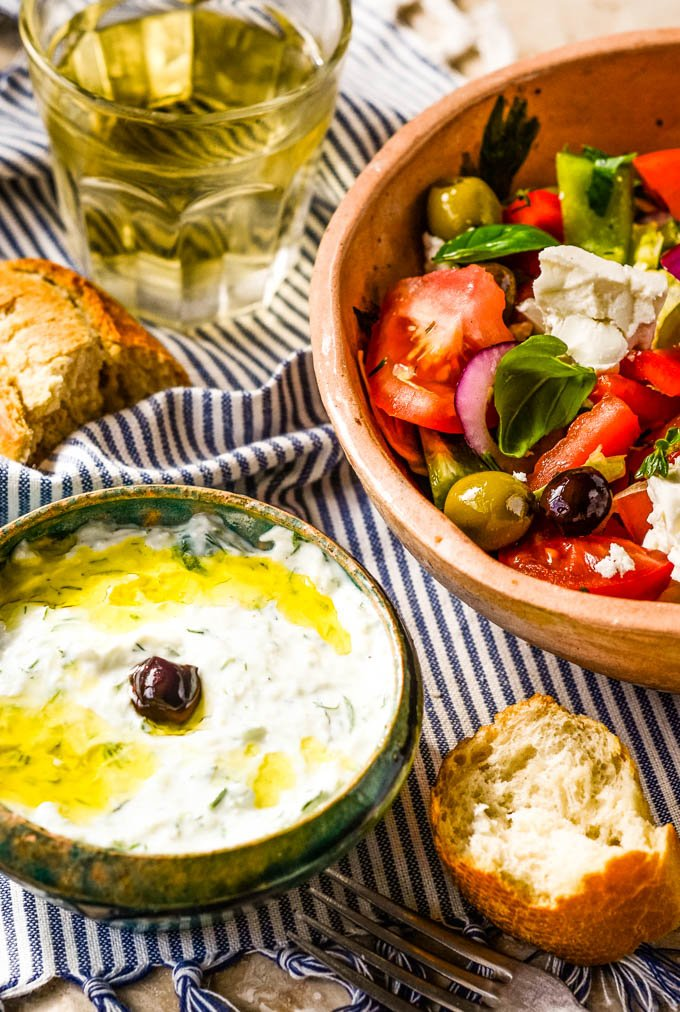 Greek salad in bowl with smaller bowl of tzatziki in front
