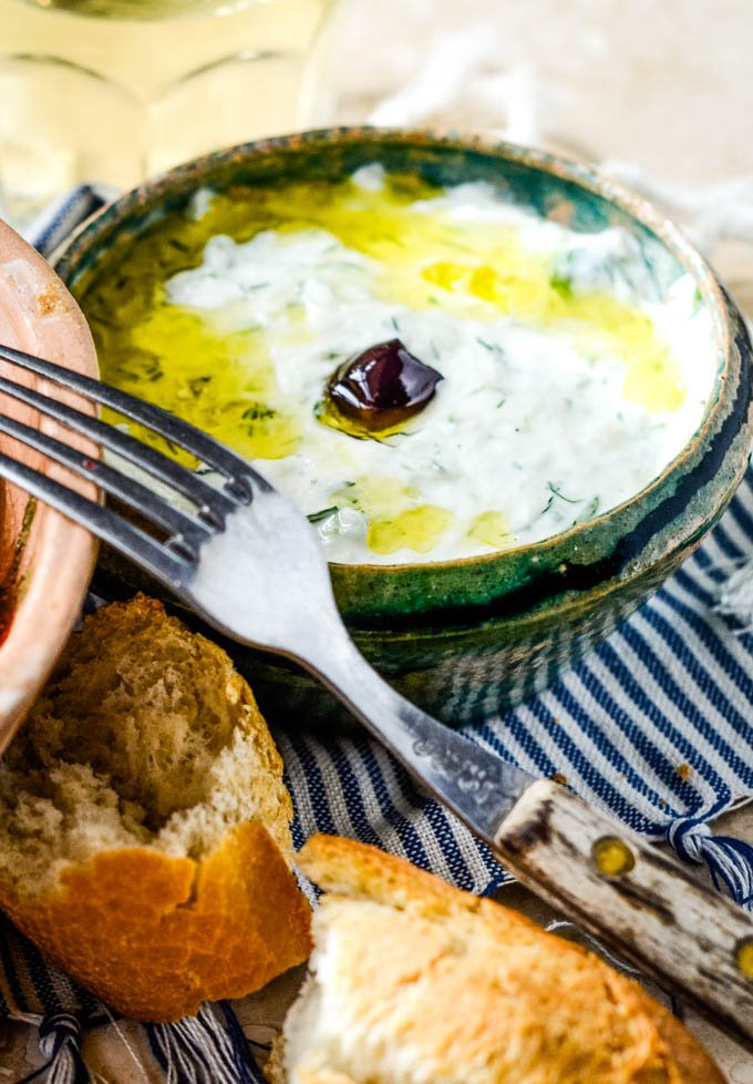 homemade tzatziki dip in blue bowl with fork beside it