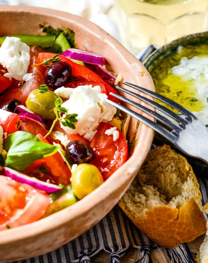 Greek salad in bowl with bread at side of plate
