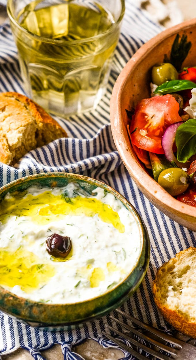 tzatziki sauce in bowl with salad bowl showing at side and glass of wine