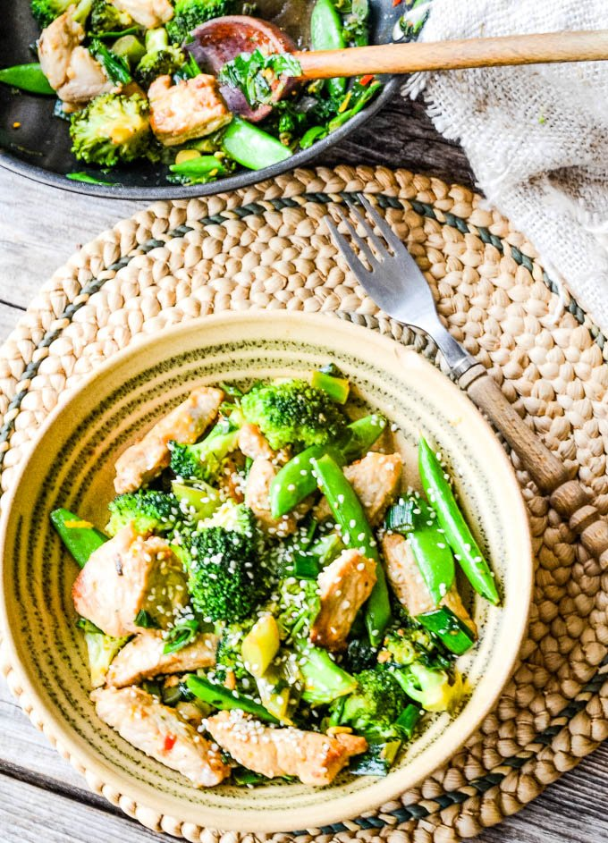 pork and broccoli stir fry with wok behind
