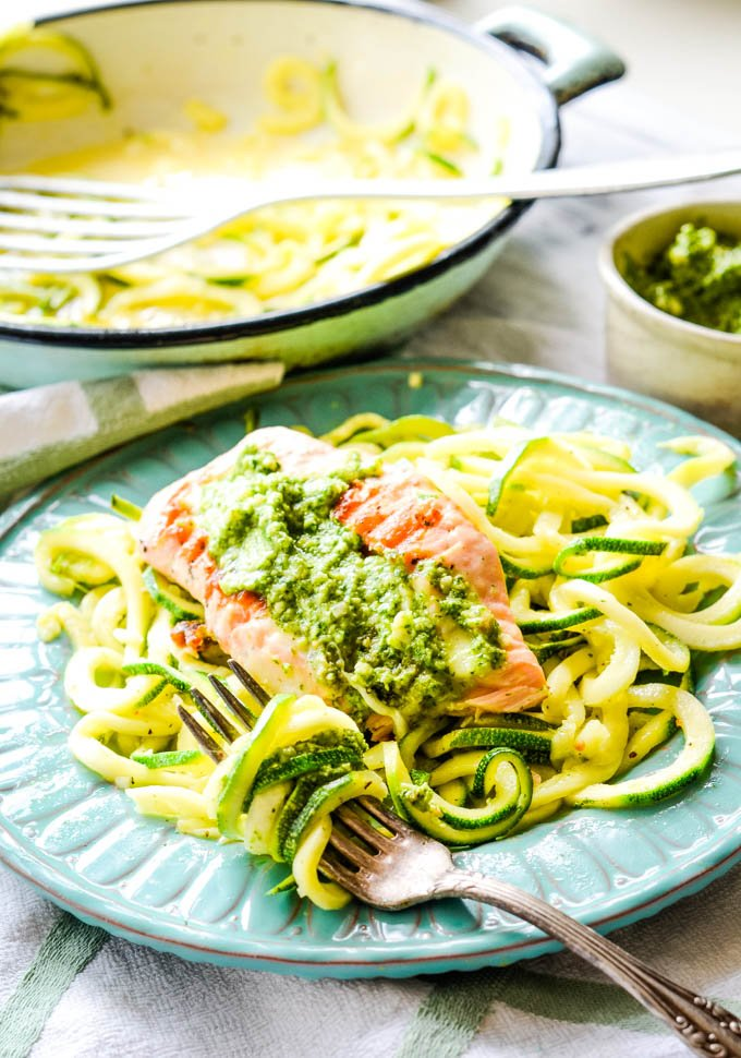 salmon with pesto on top and pan in the backgrouns
