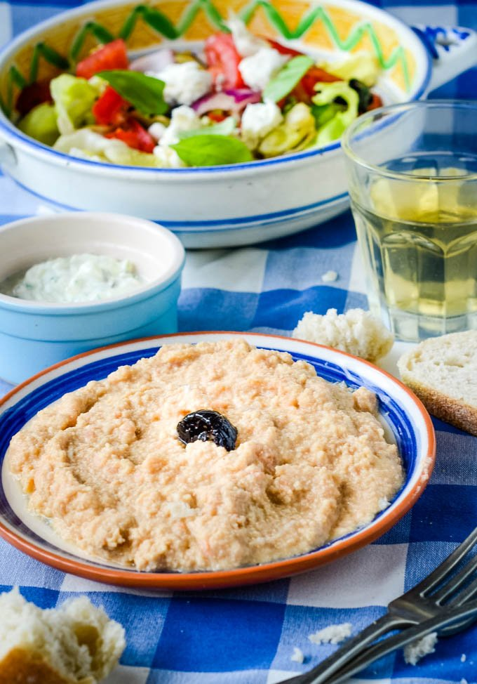 traditional Greek taramasalata (fish roe dip) in bowl on table with bread and wine behind