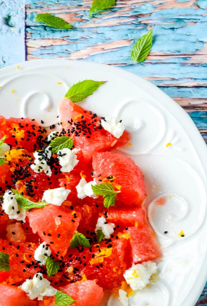 Greek watermelon and feta salad with mint on white plate on blue table