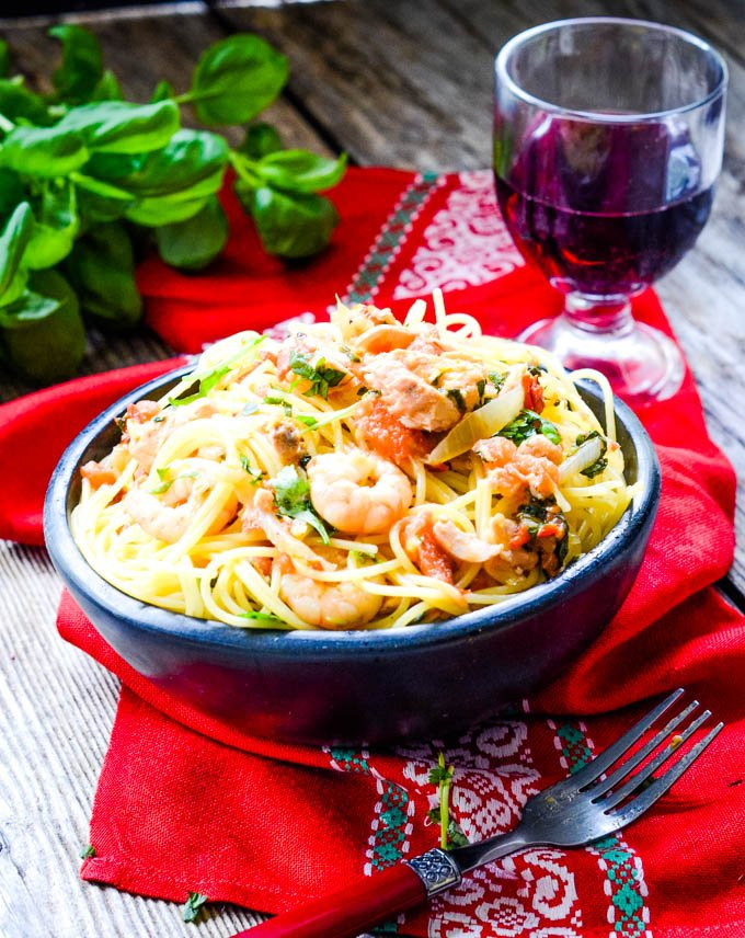 long shot of bowl of seafood pasta with red wine glass behind