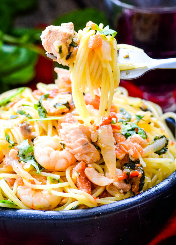 close up of fork with pasta and seafood
