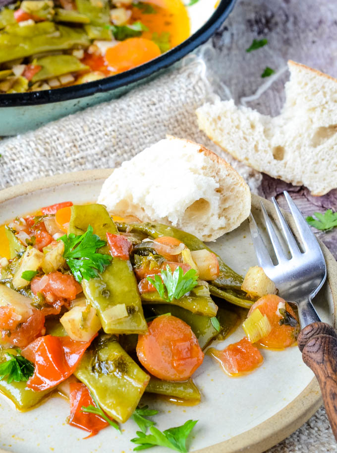 Greek warm green beans salad on plate with fork and bread