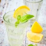 glass of lemonade with basil leaf and lemon slices