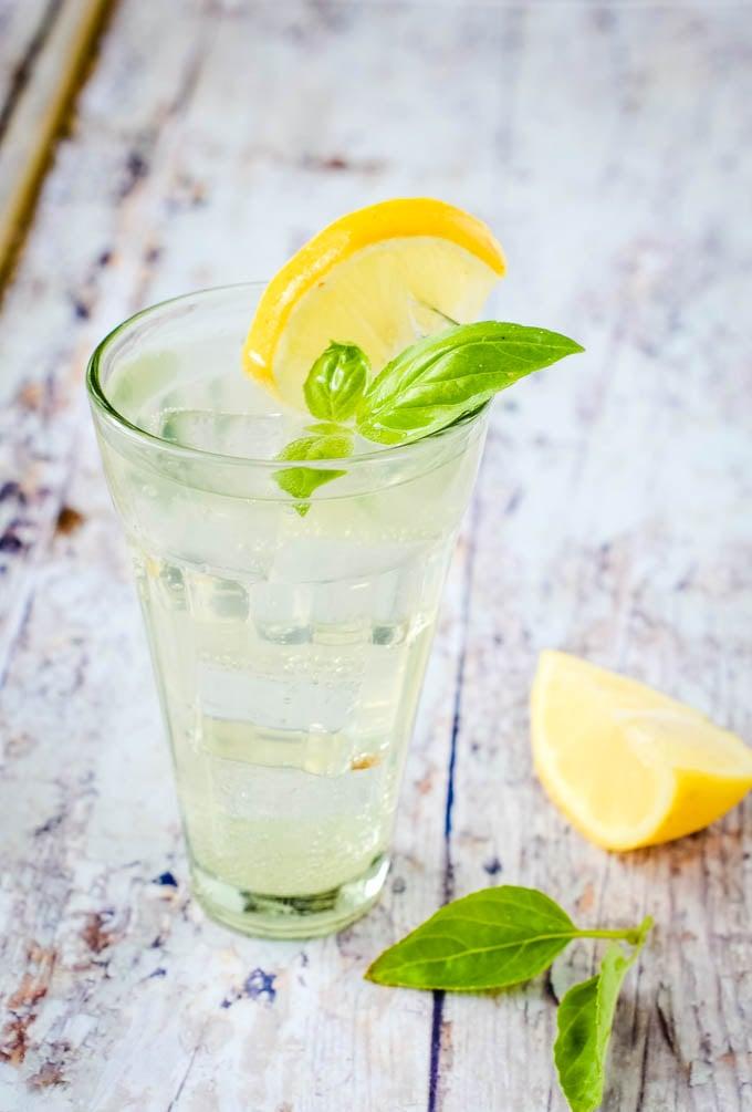 single glass of lemonade with basil and lemon