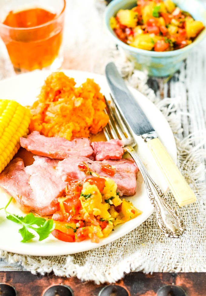 plate of baked ham and corn with salsa on side of plate