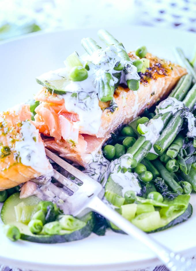 salmon with fork on plate breaking the fish