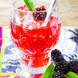 blackberry water in glass with sage leaf, berry and straw