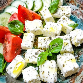homemade feta cheese in bowl with tomatoes and basil