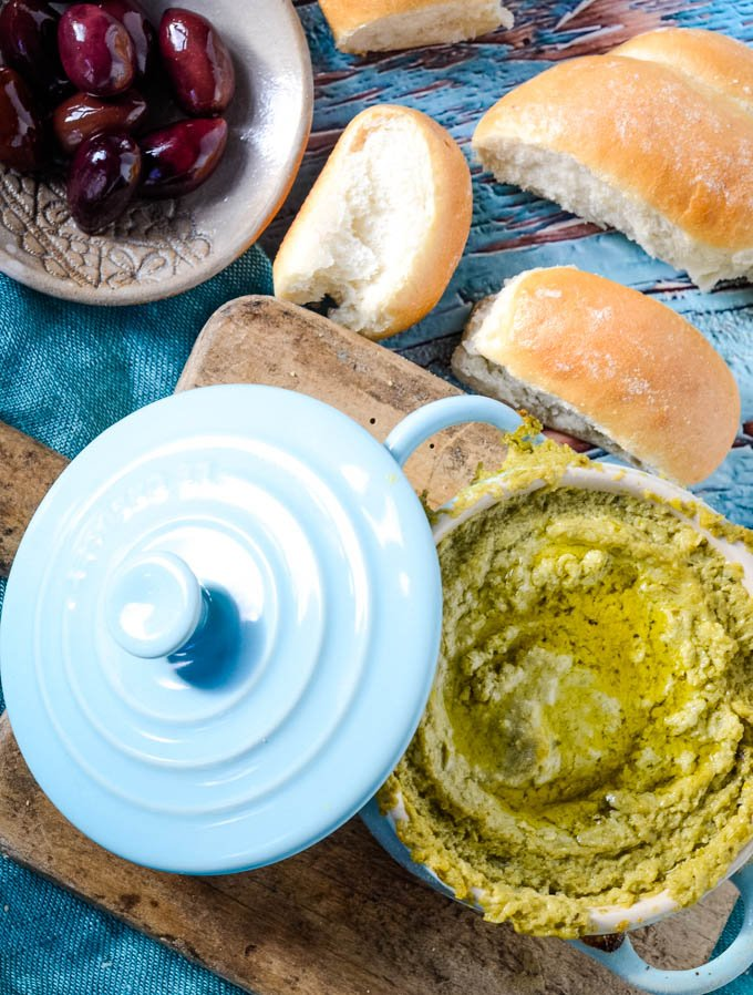 top down shot of pot of dip on table with olives and bread
