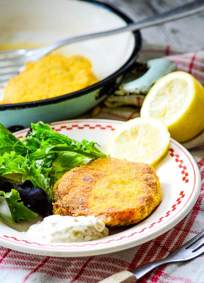 salmon fishcakes with lemons and pan behind