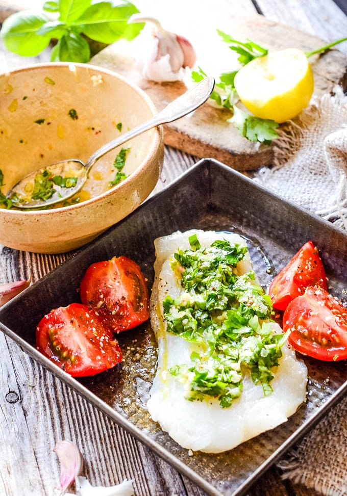 baking dish witth cod an gremolata sauce and tomatoes