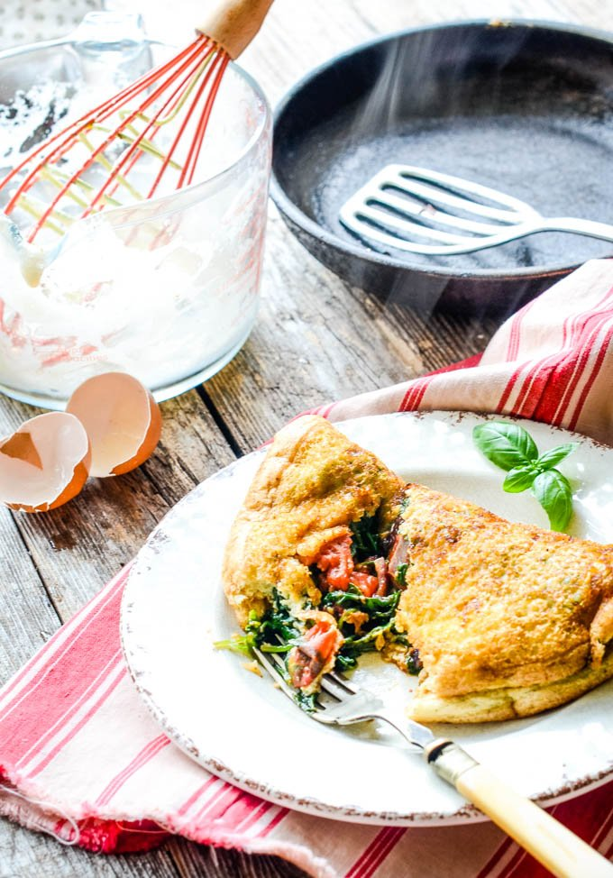 top down shot of omelette on table with pan and bowl with whisk behind