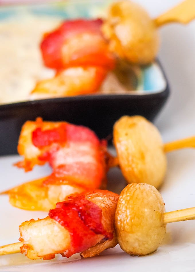 two skewers with prawns at front and one in bowl of dip behind