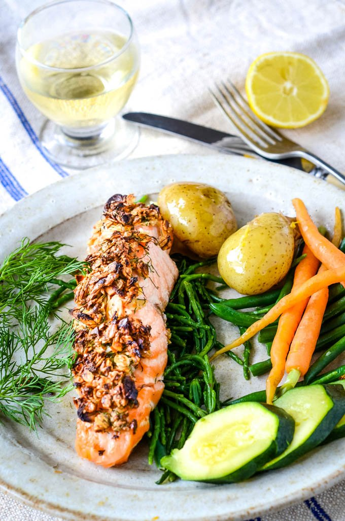 table shot of salmon on plate with glass of wine behind