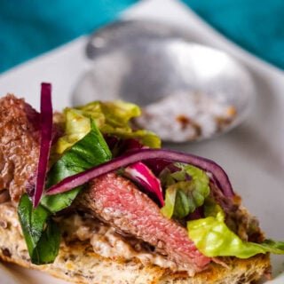 side view of steak and salad on toast