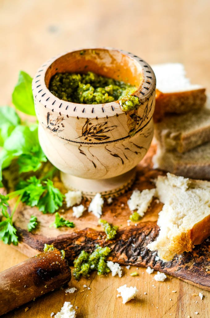 nut free pesto in wooden mortar with breadcrumbs scattered