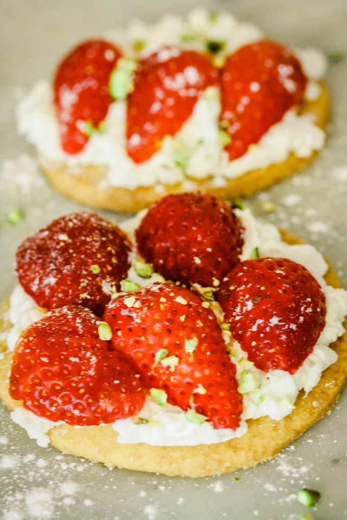 close up of strawberry shortcakes with pistachios sprinkled on top