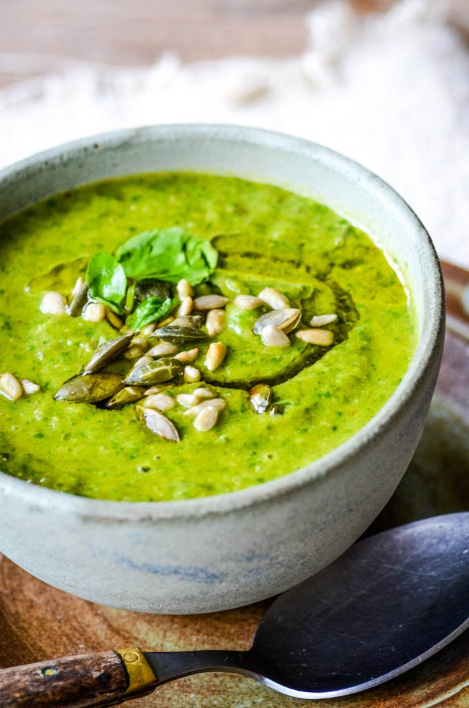 top down photo of spinach soup in bowl with spoon at side